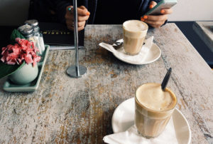 Person on phone with two cups of coffee on table