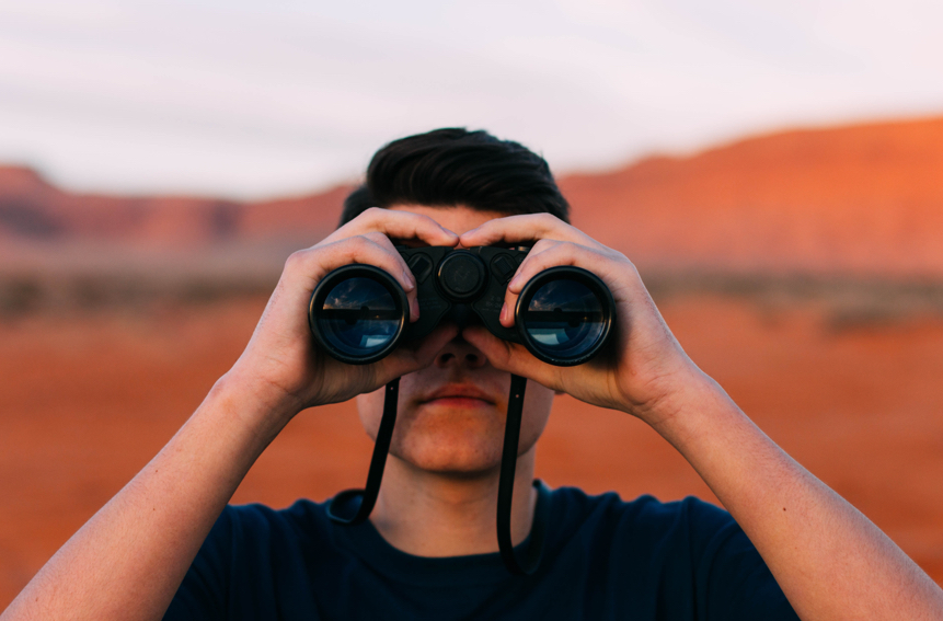 Contenet and SEO What You Need To Know. SEO Tips. Search Engine Optimization. seo. search engine optimization tips. Image of a man standing in the desert looking through binoculars.