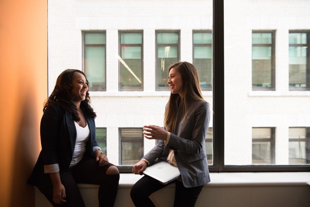 Two women sitting and talking next to a window.