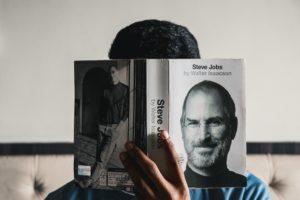 Man holding a book about Steve Jobs